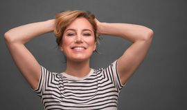 Young woman relaxing with hands behind head on gray background. stock images