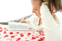 Young woman relaxing on her bed with a book Royalty Free Stock Photography
