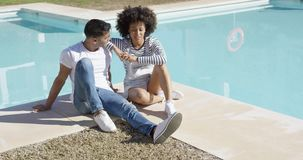 Young woman relaxing with her boyfriend poolside stock footage