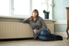 Young woman relaxing at home with cup of coffee Royalty Free Stock Images