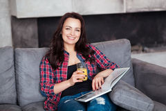 Young Woman Relaxing at Home with a Glass of Orange Juice. Beautiful girl in a casual style sits on the sofa and reads a Stock Photo