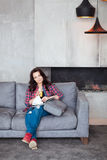 Young Woman Relaxing at Home with a Glass of Orange Juice. Beautiful girl in a casual style sits on the sofa and reads a Stock Image