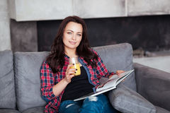 Young Woman Relaxing at Home with a Glass of Orange Juice. Beautiful girl in a casual style sits on the sofa and reads a Stock Photos