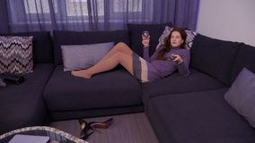 Young girl drinks wine and relaxing at home watching the tv