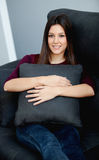 Young woman relaxing at home on her sofa Stock Images