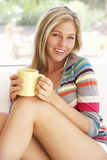 Young Woman Relaxing At Home With Hot Drink Royalty Free Stock Photos