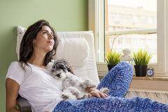 Young woman relaxing at home hugging her small dog royalty free stock photo