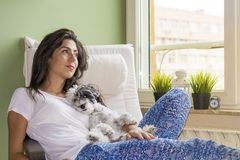 Young woman relaxing at home hugging her small dog Royalty Free Stock Photography