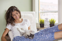 Young woman relaxing at home hugging her small dog Stock Photo