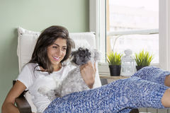 Young woman relaxing at home hugging her small dog Stock Images