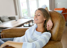 Young woman relaxing at home in leather chair Stock Image