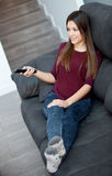 Young woman relaxing at home watching TV Royalty Free Stock Images