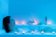 Young woman relaxing in hot foam bath. Close up portrait of young woman relaxing in hot foam bath at home.Low key blue ambient with decorative candles along Royalty Free Stock Images