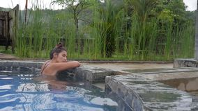 Young Woman Relaxing in Hot Spring Pool in Thailand. Girl Enjoying Bathing in Geothermal Spa Tourist Attraction. HD. stock video footage