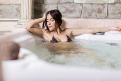 Pretty young woman relaxing in the hot tub. Young woman relaxing in the hot tub royalty free stock images
