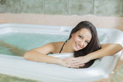 Young woman relaxing in the hot tub Stock Images