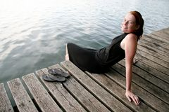 Young woman relaxing at lake. A young woman in a black dress relaxing on a wooden peer at a lake Stock Photography