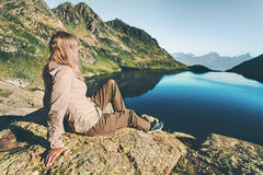 Young Woman relaxing at lake in mountains. Travel Lifestyle wanderlust concept summer vacations outdoor harmony with nature Stock Photography