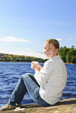 Young woman relaxing at lake shore. Young woman sitting with beverage on rock relaxing by beautiful lake in Algonquin Park, Canada Stock Photo