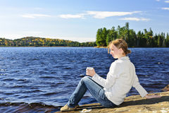 Young woman relaxing at lake shore. Young woman sitting with beverage on rock relaxing by beautiful lake in Algonquin Park, Canada Stock Images