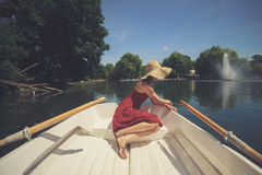 Young woman relaxing on the lake. A young woman is sitting in a boat on the lake and is relaxing on a sunny day Royalty Free Stock Image