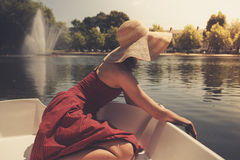 Young woman relaxing on the lake. A young woman is sitting in a boat on the lake and is relaxing on a sunny day Royalty Free Stock Images