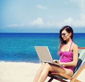 A young woman relaxing with a laptop on a beautiful beach. Young, beautiful, sporty and sexy woman with the notebook pc relaxing on the beach Stock Photography
