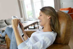 Young woman relaxing in leather armchair wtih tablet Stock Photography