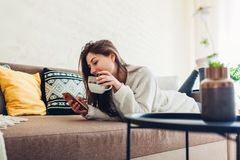 Young woman relaxing in living room using smartphone and drinking coffee. Interior decor stock photos