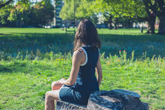 Young woman relaxing on log in park Royalty Free Stock Photography