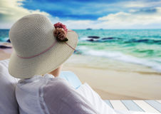 Young woman relaxing and looking sea on bed at the beach Royalty Free Stock Photo