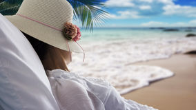 Young woman relaxing and looking sea in bed on the beach Royalty Free Stock Images