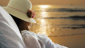 Young woman relaxing and looking sunrise in bed on the beach Stock Image