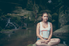 Young woman relaxing in lotus pose on the rocks nearby waterfall with mysterious Mona Lisa smile Royalty Free Stock Photo