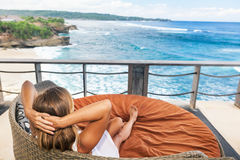 Young woman relaxing in lounge on veranda with sea view. Young happy woman relaxing in lounge on roof veranda with beautiful tropical sea view. Positive girl Royalty Free Stock Photography