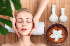 Young woman relaxing with massage in spa Stock Photos
