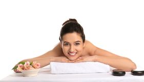 Young woman relaxing on massage table against white background. Spa procedures stock photo