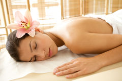 Young woman relaxing on massage table, eyes closed Stock Images