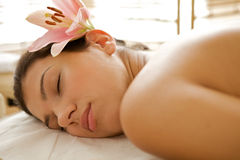 Young woman relaxing on massage table, eyes closed Royalty Free Stock Photography