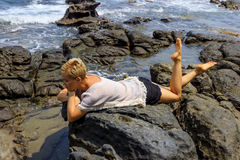 Young woman relaxing and meditating on picturesque rocky seashore. View 5 Stock Images