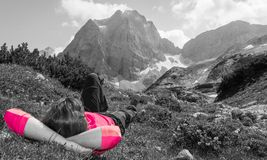 Young woman relaxing in a mountain meadow in isolated colors Stock Images