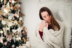 Young woman relaxing with a mug of coffee as she cuddles up in warm blanket on ancient commode. Her eyes closed and Royalty Free Stock Photo