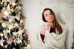 Young woman relaxing with a mug of coffee as she cuddles up in warm blanket on ancient commode. Her eyes closed and Stock Photos