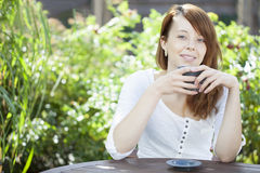 Young woman relaxing with a mug of coffee Stock Images