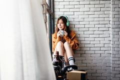 Young Woman Relaxing with Music From Headphone in Cozy House, En. Joying with Morning Sunshine from Window and Hot Coffee Royalty Free Stock Image