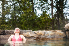Young Woman Relaxing in a Nordic Spa. Young Woman Relaxing in a Outdoor Nordic Spa, in the forest Stock Image