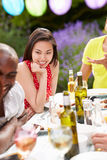 Young Woman Relaxing At Outdoor Barbeque Royalty Free Stock Photography