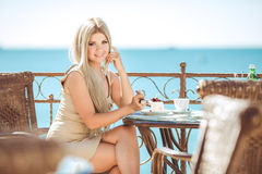 Young woman relaxing in an outdoor cafe Stock Images