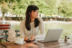 Young woman relaxing at outdoor coffee shop Stock Photography