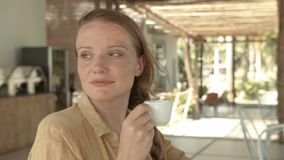 Beautiful woman drinking espresso in restaurant while waiting for somebody. stock video
